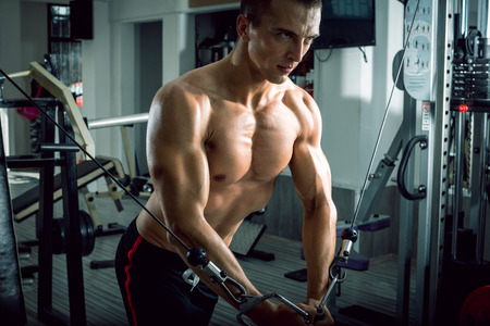Man doing cable fly exercise in gym Stock Photo