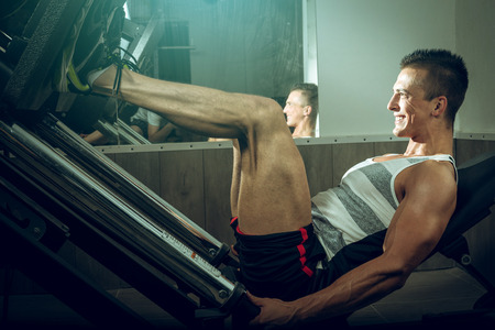 Man working out on leg press machine in gym