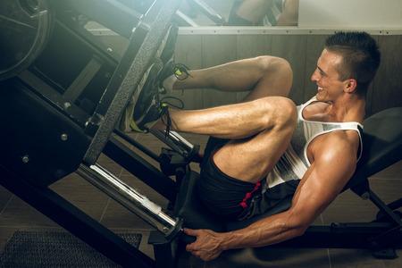 piernas hombre: Hombre que se resuelve en la pierna máquina de la prensa en el gimnasio Foto de archivo