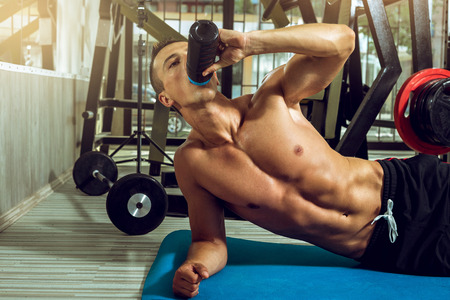 Man drinking protein shake mix while doing side plank exercise.