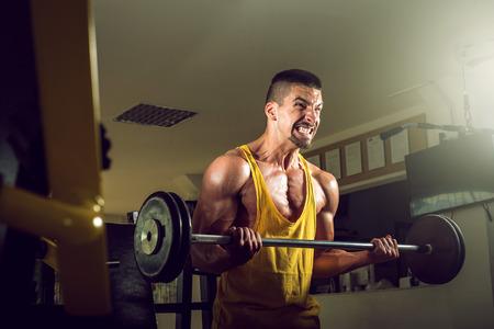 levantar pesas: Yougn adolescentes hombre que hace ejercicio pesas en el gimnasio