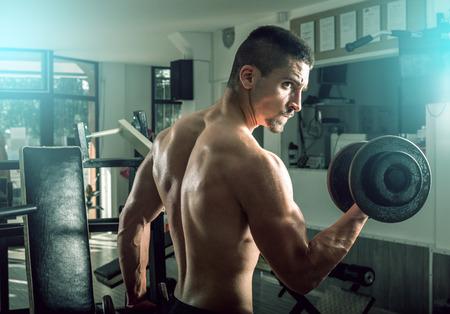 levantando pesas: Hombre joven adolescente adulta haciendo flexiones de bíceps con mancuernas en el gimnasio