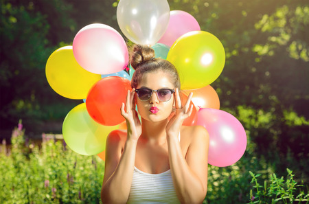 Girl with balloons in nature making facial expressions Standard-Bild