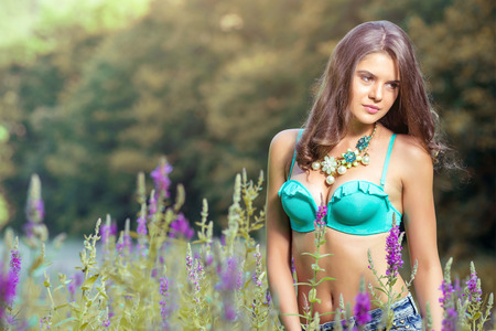 Beautiful young girl standing in high grass and flowers on river bank wearing bra and jeans shorts.