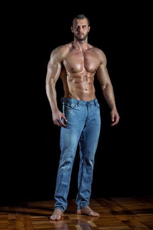 Man posing wearing jeans in front of black backgroud