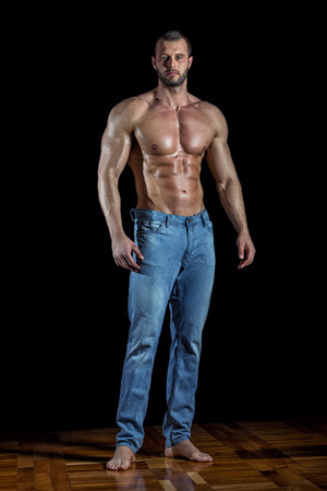 Man posing wearing jeans in front of black backgroud