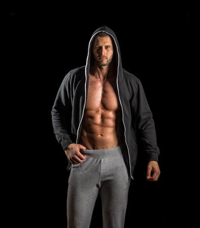 abdominal fitness: Hombre adulto joven que presenta en gimnasia vistiendo sudadera con capucha Foto de archivo
