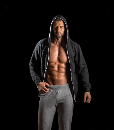 sexy abs: Young adult man posing in gym wearing hoodie Stock Photo