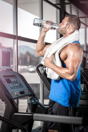 Junge erwachsene Mann trinkt eine Flasche Wasser auf Gewindefräser in Fitness-Studio.