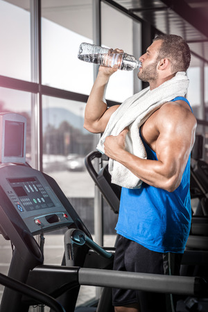 muscular man: Young adult man drinking bottle of water on threadmill in gym.