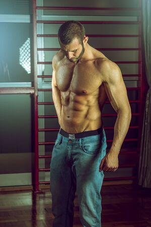 seins nus: Homme posant porter des jeans en salle de gym Banque d'images