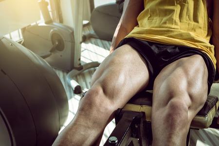 piernas hombre: Hombre adulto joven que hace ejercicio de la pierna ejercicios de extensión en el gimnasio