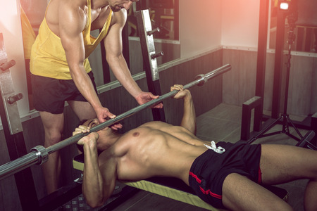man power: A handsome young muscular sports man doing weight lifting and gets help from his friend who is personal trainer. Stock Photo