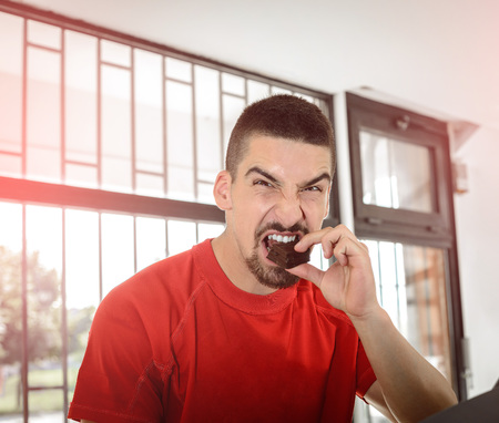 young adult man: Young adult man bites chocolate bar during gym workout training