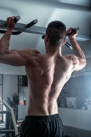 pull up: Giovane uomo adulto che fa tirare esercizio in palestra. Archivio Fotografico