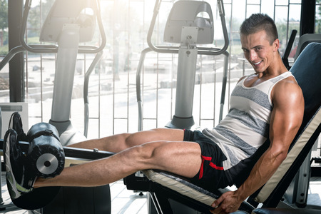 Young adult man doing leg extension workout exercise in gym Stock Photo