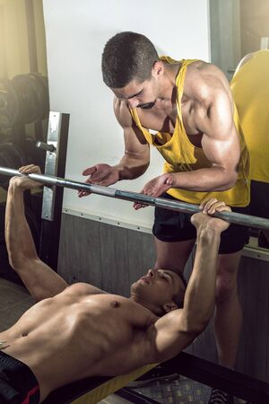 muscle guy: A handsome young muscular sports man doing weight lifting and gets help from his friend who is personal trainer. Stock Photo
