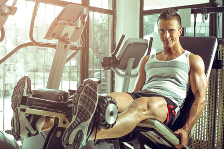 sports training: Young adult man doing leg extension workout exercise in gym Stock Photo