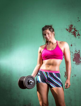 curls: Athletic girl doing dumbbell curls in gym