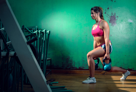 cross leg: Young adult caucasian girl doing lunge exercise indoor with kettlebell.