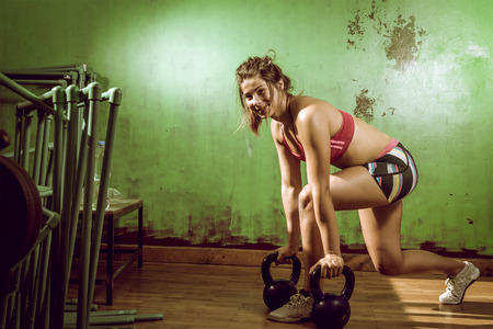 cross: Young adult caucasian girl doing lunge exercise indoor with kettlebell.