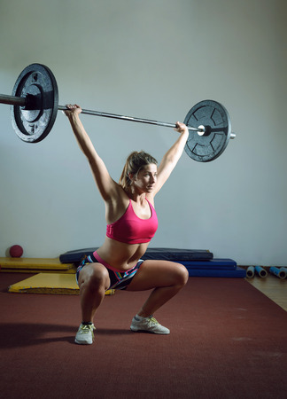 lifestyle caucasian: Young adult girl doing heavy duty  squats in gym with barbell
