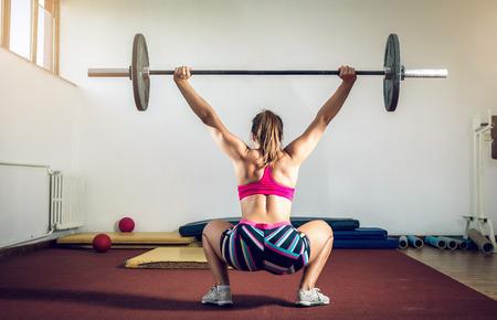 squatting: Muchacha adulta joven que hace sentadillas para uso industrial en el gimnasio con mancuerna