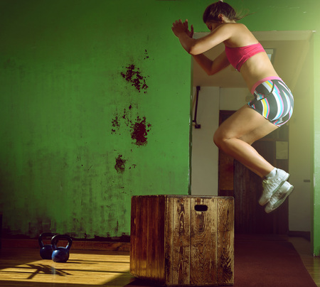 jump: Young adult crossfit girl jumping on box in gym club. Stock Photo