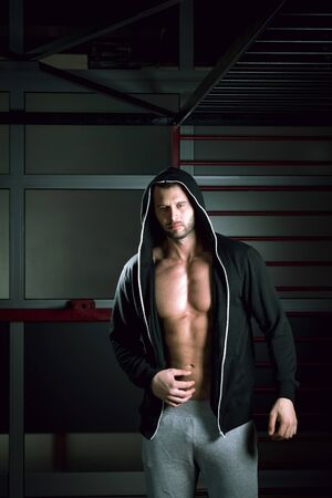 hoodie: Young adult man posing in gym wearing hoodie Stock Photo