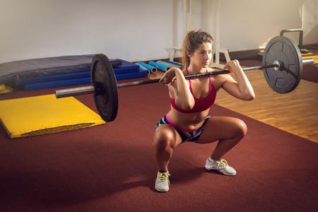 Junge erwachsene Mädchen tun schwere Kniebeugen im Fitness-Studio mit Hantel