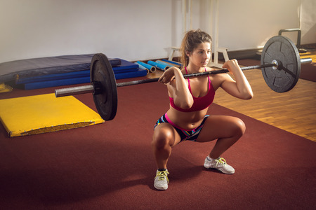 mujeres fitness: Muchacha adulta joven que hace sentadillas para uso industrial en el gimnasio con mancuerna