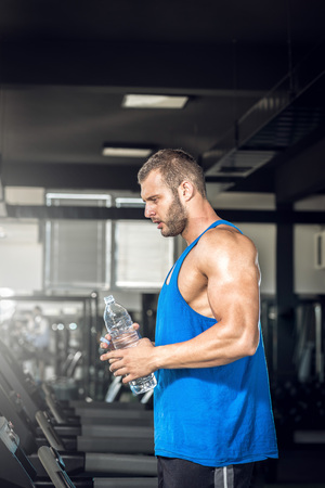 bebiendo agua: Hombre adulto joven que bebe una botella de agua en threadmill en el gimnasio.