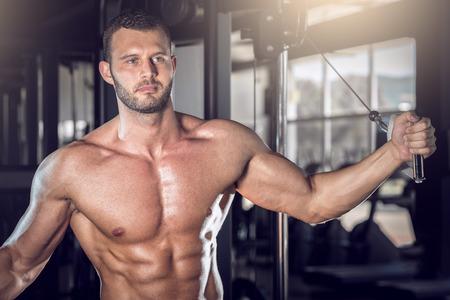 hombre fuerte: Hombre adulto joven que hace mosca cable en el gimnasio. Foto de archivo