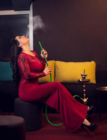 women smoking: Young attractive girl in elegant dress smoking narghile hookah in bar