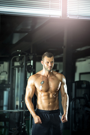 strong men: Young adult man doing bicep curls and posing in gym
