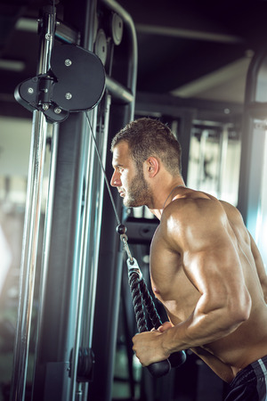 Young adult man doing triceps rope pushdown exercise in gym.