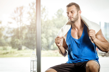 bel homme: Young adult man relaxing after workout in gym. Banque d'images