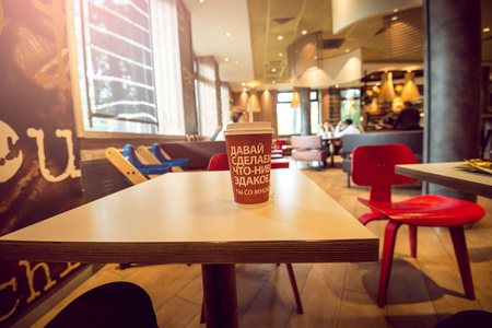 MOSCOW, RUSSIA - OCTOBER 02, 2015: McCafe coffee bar interior in Moscow, Russia with plastic cup of coffee in first focus. McCafe is subsidiary brand of World's most famous fast food restaurant chain - McDonalds.