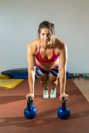 pushup: Crossfit fitness woman push ups Kettlebells pushup exercise at gym workout