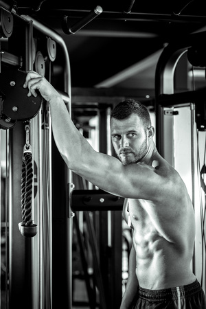 muscle guy: Young adult man posing in gym