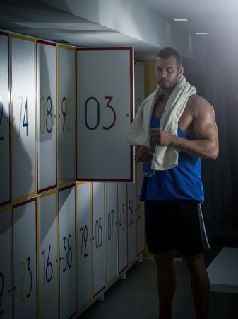 gym room: Young adult fit man standing in locker room and opening locker door. Stock Photo