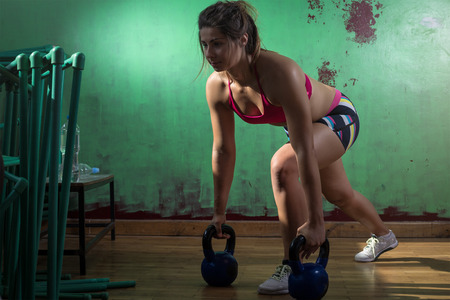 lunge: Young adult caucasian girl doing lunge exercise indoor with kettlebell.