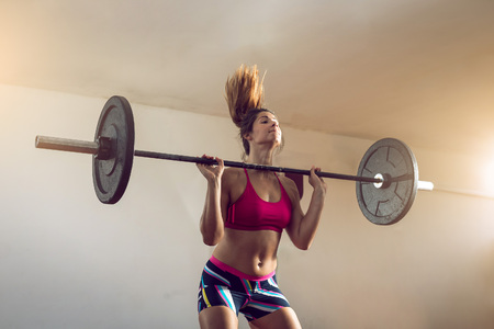 sports bar: Young adult girl doing heavy weightlifting during cross fit exercise