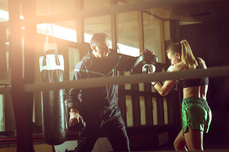 Young adult woman doing kickboxing training with her coach. Stock Photo