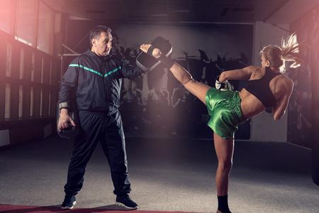 Giovane donna adulta facendo calcio alto durante l'esercizio di allenamento kickboxing