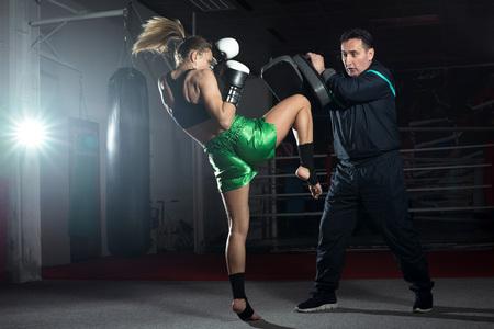 boxeador: Muchacha que hace ejercicio Retroceso de la rodilla durante el entrenamiento de kickboxing con entrenador personal