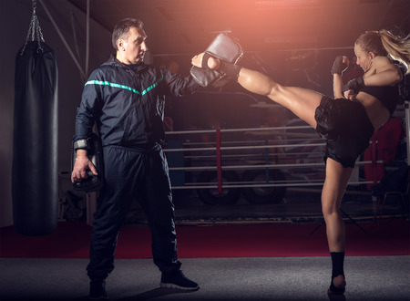 Young adult sexy woman doing back leg high kick during kickboxing exercise with trainer Foto de archivo
