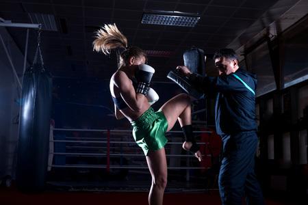 Muchacha que hace ejercicio Retroceso de la rodilla durante el entrenamiento de kickboxing con entrenador personal Foto de archivo - 55232748