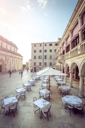 Restaurant with white table clothes in Sibenik old town, Croatia