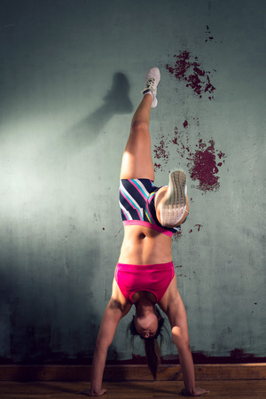 muscle girl: Young adult gymnastic fit girl is standing on hands next to a wall